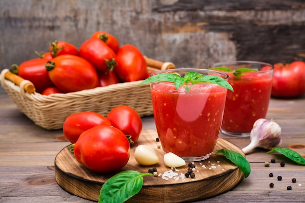 Suco de tomate fresco com folhas de manjericão em copos e tomates em uma mesa de madeira