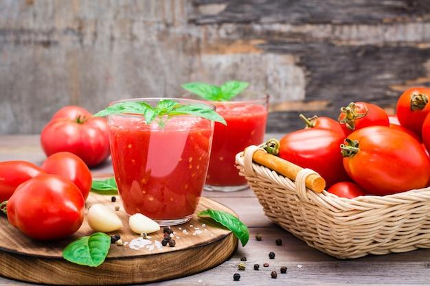Suco de tomate fresco misturado com folhas de manjericão em copos e ingredientes para a sua preparação em uma mesa de madeira