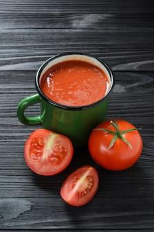 Suco de tomate na caneca verde do esmalte