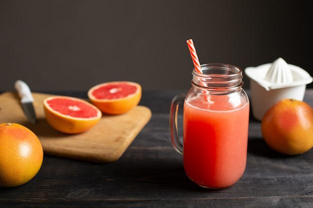 Suco de toranja espremido na hora em uma jarra com alça. sobre uma mesa de madeira preta estão as toranjas inteiras e fatiadas e o espremedor manual branco.