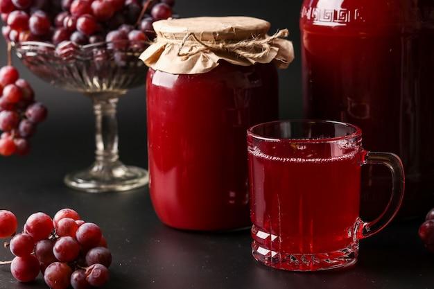 Suco de uva em um copo e latas, cozidas em um espremedor, colhendo suco de uma colheita de uva localizada em fundo escuro