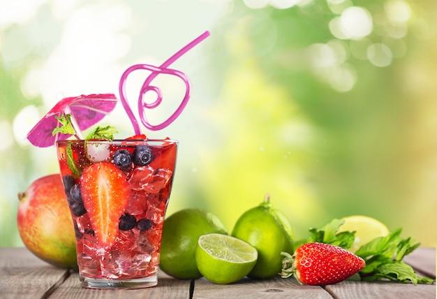 Suco delicioso com frutas frescas em vidro no fundo