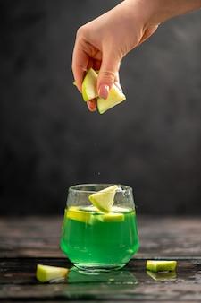 Suco delicioso em uma mão de vidro, colocando limão de maçã em um fundo escuro