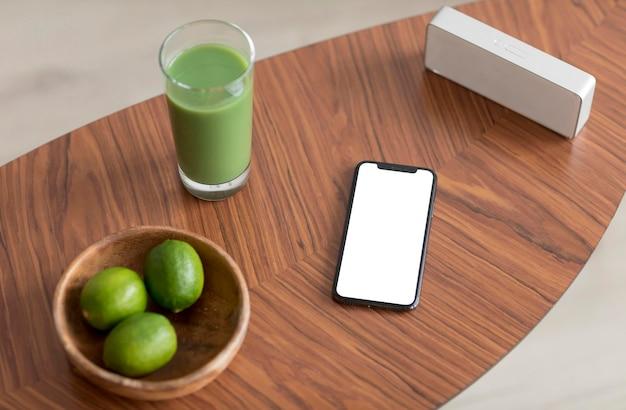 Suco desintoxicante e smartphone com tela em branco em uma mesa de madeira