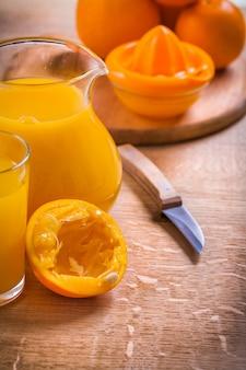 Suco em jarra de vidro faca espremedor de frutas na mesa de madeira