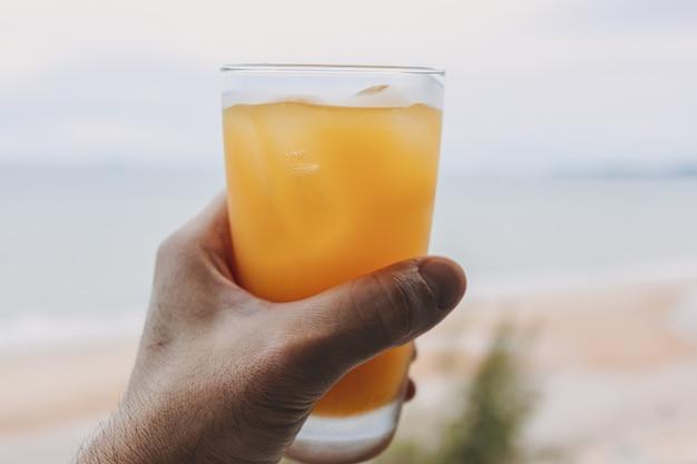 Suco em um copo com vista para o mar no conceito de verão