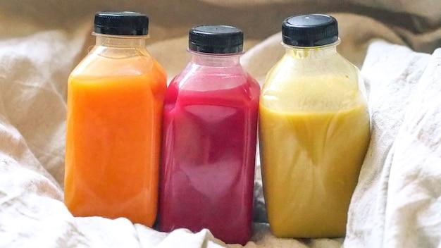 Suco em uma garrafa em fundo de linho. idéia de conceito natural. bebida saudável em garrafa de plástico transparente.