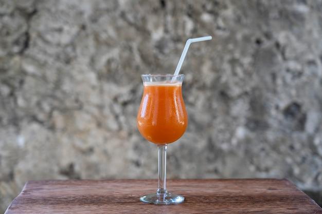 Suco espremido na hora de frutas tropicais em uma taça de vidro no fundo de uma velha parede de pedra. ilha de zanzibar, tanzânia, áfrica oriental. close up, copie o espaço