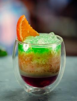 Suco exótico com gelo verde barbear com fatia de laranja por cima