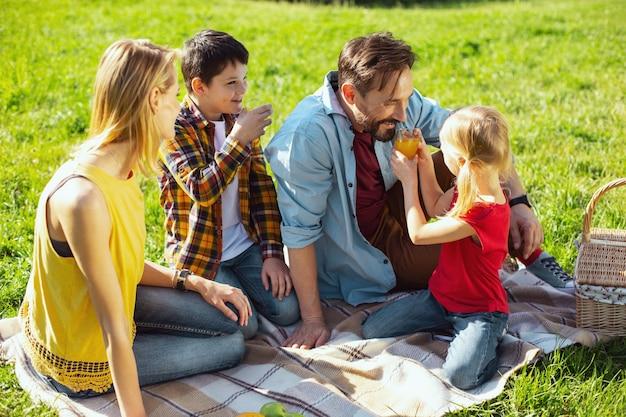 Suco favorito. pai alegre de cabelos escuros sorrindo e bebendo um pouco de suco com os filhos