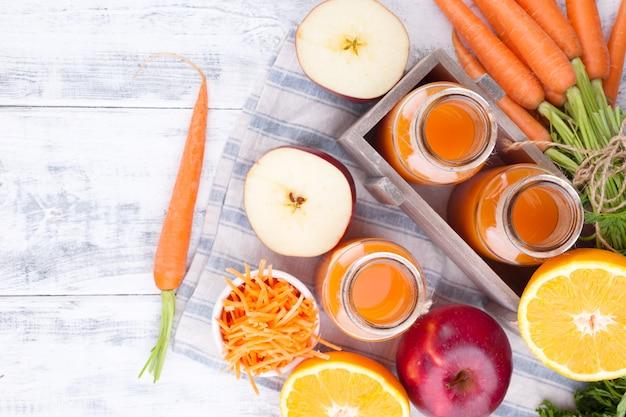 Suco fresco de cenoura, maçã, laranja e limão. cenouras com folhas e outras frutas frescas em um fundo branco de madeira