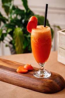 Suco fresco de cenoura saudável em copos elegantes em um fundo de madeira. autênticas opções de bebidas da cozinha mediterrânea no menu.