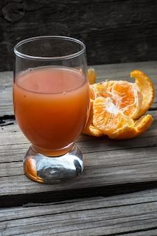 Suco fresco de citrinos tropicais no fundo de madeira.