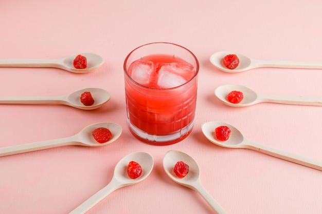 Suco gelado em um copo com cereja seca vista de alto ângulo em uma superfície rosa