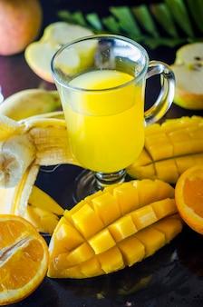 Suco multivitamínico e multifruta em uma xícara de frutas de variedade média na mesa
