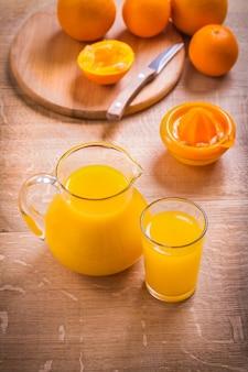 Suco na jarra de vidro faca frutas espremedor na mesa de madeira