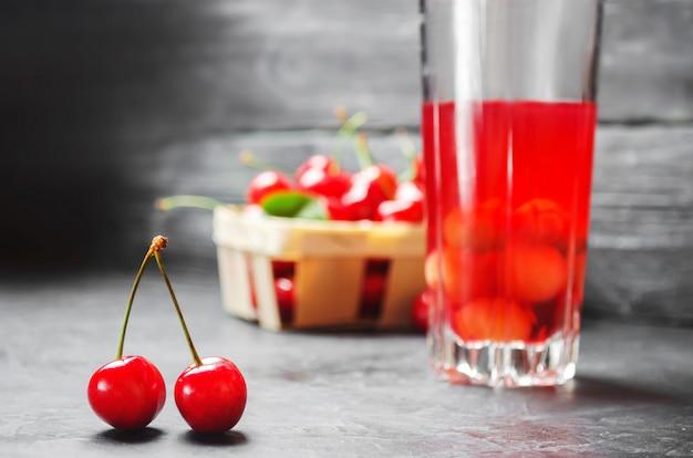 Suco ou compota com cerejas. cereja vermelha madura fresca em uma cesta em um backg concreto cinzento
