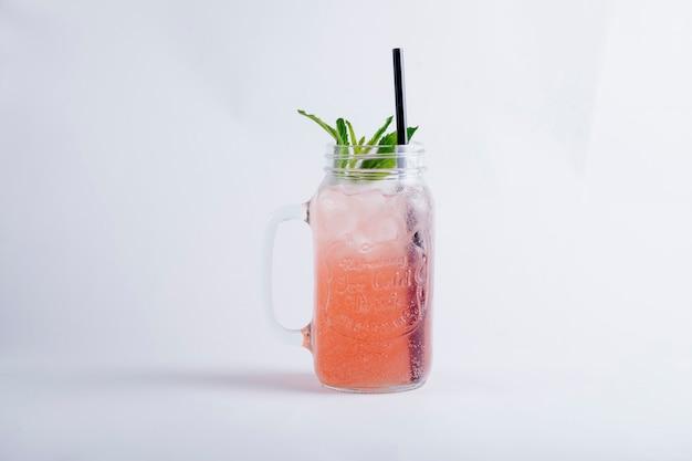 Suco rosa com cubos de gelo e hortelã dentro do frasco de vidro.