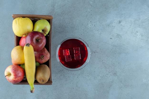 Suco saboroso com cubos de gelo e frutas diversas.