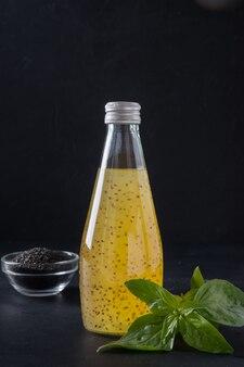 Suco tropical laranja com sementes de manjericão em garrafa no preto. fechar-se.