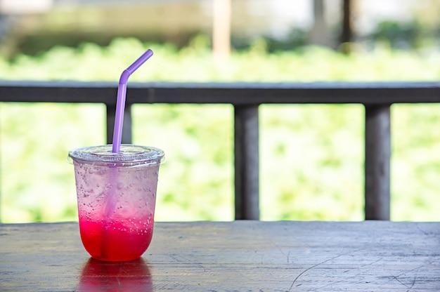 Suco vermelho com gelo em um copo de plástico na mesa