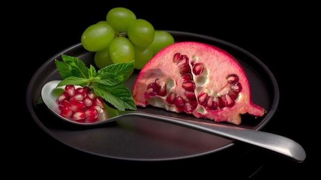 Suco vermelho de romã na mesa escura, romã madura fresca, romã fresca com uva