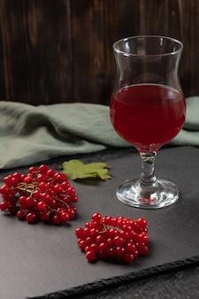 Suco vermelho de viburnum em um copo em uma haste em uma mesa escura. perto de bagas de viburnum e guardanapo de linho. comida saudável. copie o espaço