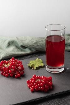 Suco vermelho de viburnum em um copo sobre uma mesa de luz. perto de bagas de viburnum e pano de linho. comida saudável. copie o espaço