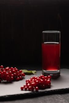 Suco vermelho de viburnum em um copo sobre uma mesa preta. perto de bagas de viburnum. comida saudável. vista frontal. copie o espaço