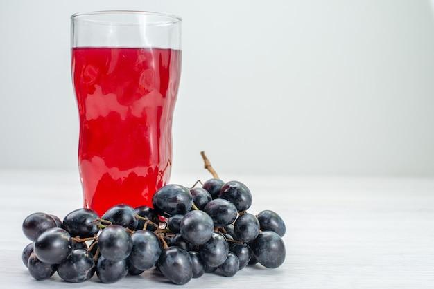 Suco vermelho de vista frontal com uvas na superfície branca suco de coquetel de frutas