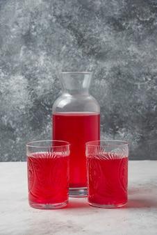Suco vermelho em copos e jarra.