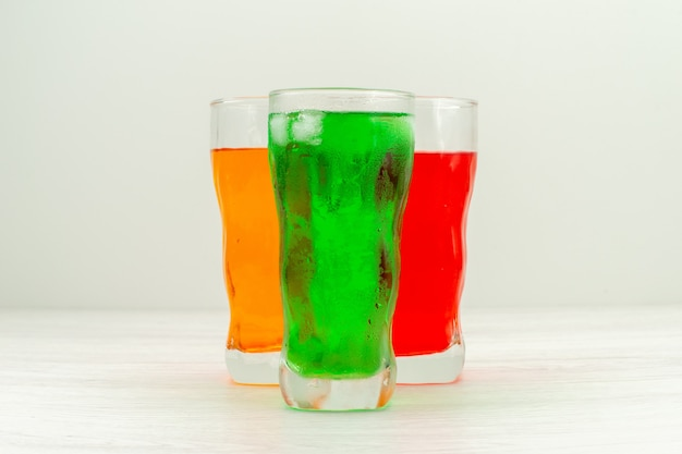 Sucos coloridos de vista frontal dentro de copos longos na superfície branca