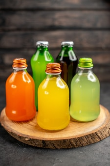 Sucos de cores diferentes em garrafas na placa de madeira na superfície de madeira escura da vista inferior