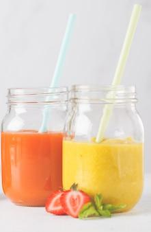 Sucos de frutas multicoloridos ou smoothie em potes de vidro e ingredientes, isolados no branco.