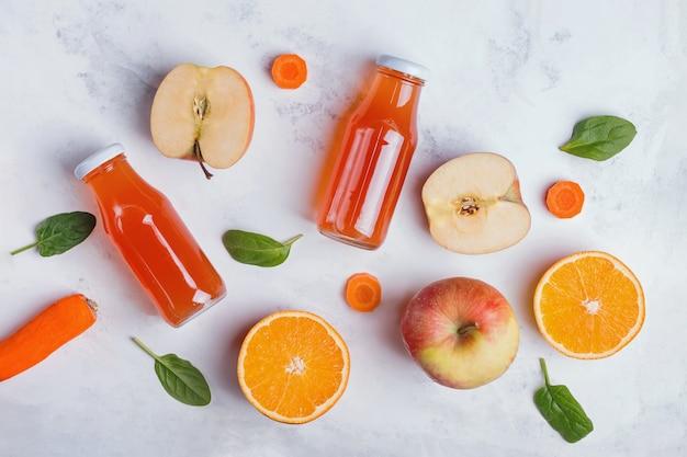 Sucos de frutas saudáveis, maçãs e laranjas na vista de mesa branca