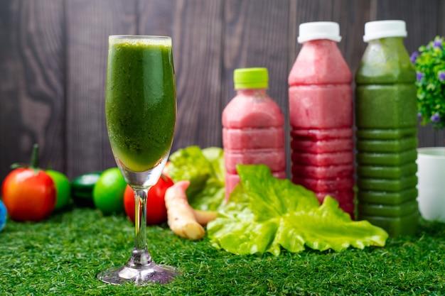 Sucos de vegetais saudáveis com frutas na grama