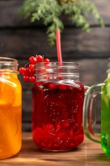 Sucos frescos orgânicos em garrafas servidas com tubos e frutas em um fundo de madeira marrom