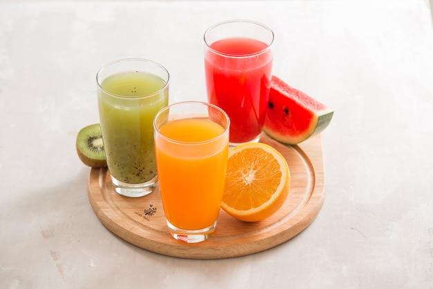 Sucos frescos smoothie três copos vermelho verde laranja laranja frutas tropicais