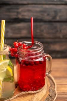 Sucos naturais de frutas orgânicas em garrafas servidas com tubos em uma tábua de madeira
