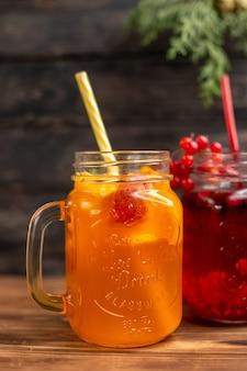 Sucos naturais frescos em garrafas servidas com tubos e frutas em um fundo de madeira marrom