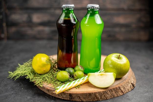 Sucos verdes e pretos em frascos de maçã, limão, pipetas de feijoas em tábua de madeira
