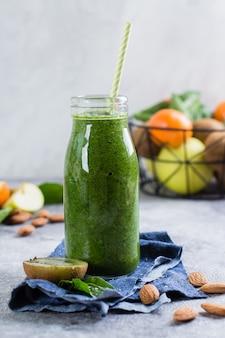 Sucos verdes frescos ou smoothies em garrafa com frutas e amêndoa de nozes no fundo cinza concreto
