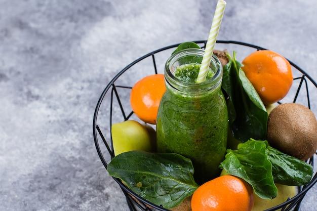 Sucos verdes ou smoothies com kiwi, espinafre, maçã verde, amêndoa cítrica e porca na cesta de metal