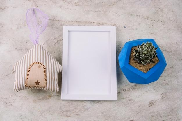 Suculenta no pote de concreto azul, casa de brinquedo de pelúcia e quadro mock up branco sobre uma mesa de mármore
