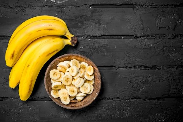 Suculentas bananas frescas e fatias de banana em um prato. sobre fundo rústico.