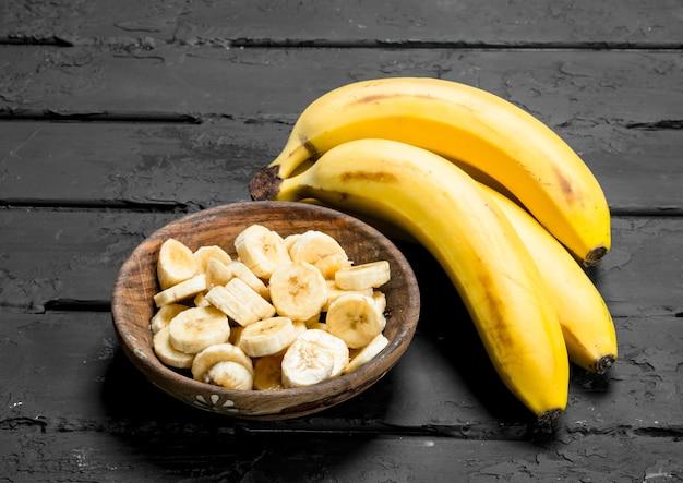 Suculentas bananas frescas e fatias de banana em um prato.