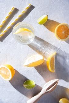 Suculentas fatias de limão e lima e um copo de água mineral com limão em uma mesa branca com duras sombras de manhã. vista do topo