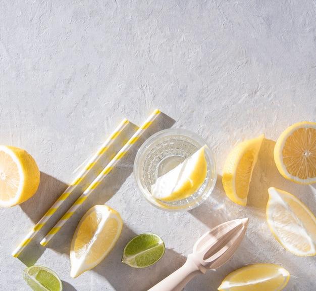 Suculentas fatias de limão e lima e um copo de água mineral com limão em uma mesa branca com duras sombras de manhã. vista superior e espaço de cópia