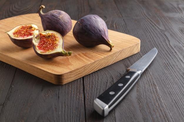 Suculentas frutas frescas de figo inteiro e um corte os figos na tábua de madeira em fundo escuro