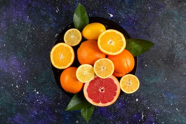 Suculentas frutas frescas inteiras ou meio cortadas sobre mesa escura.